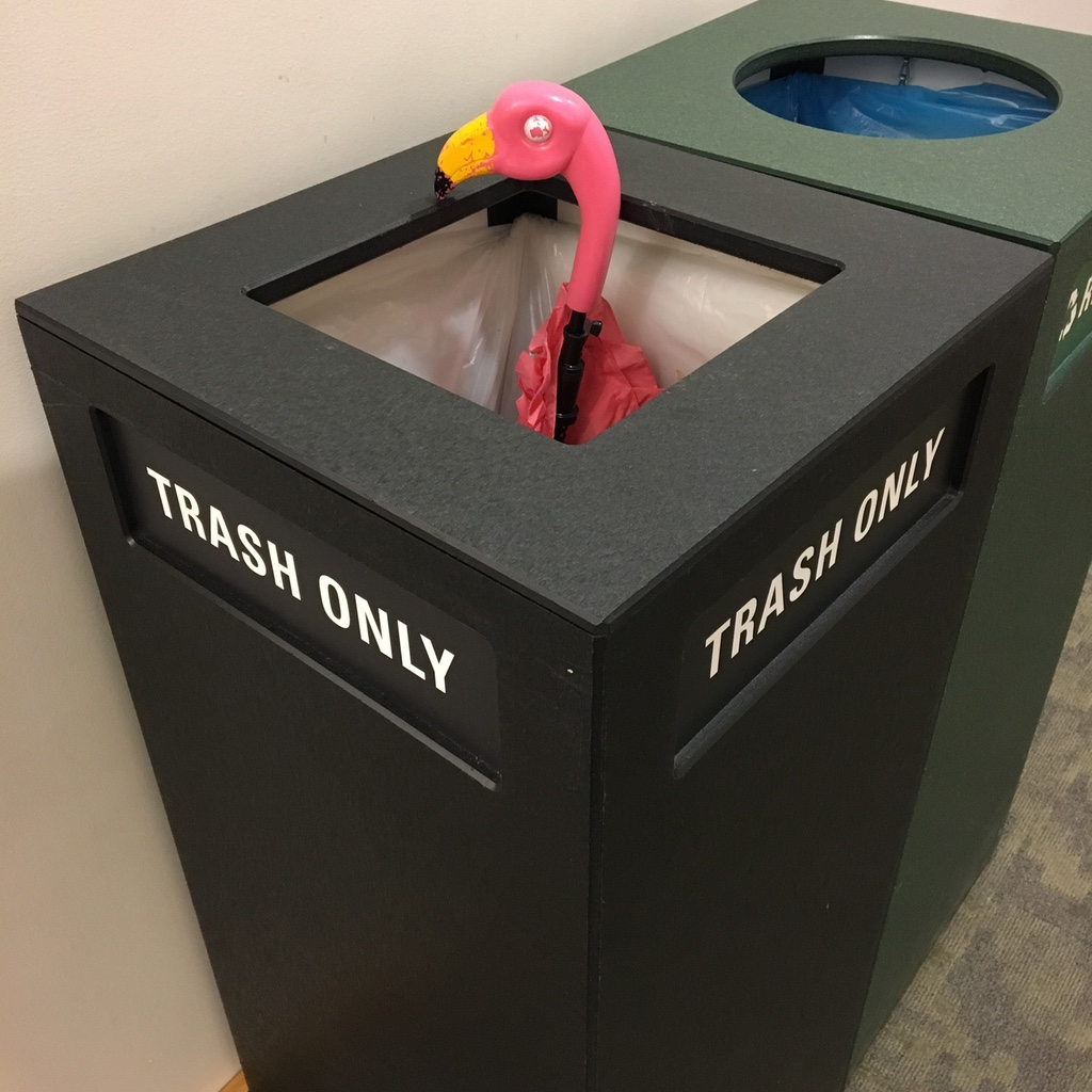 Pink flamingo umbrella in a trash can