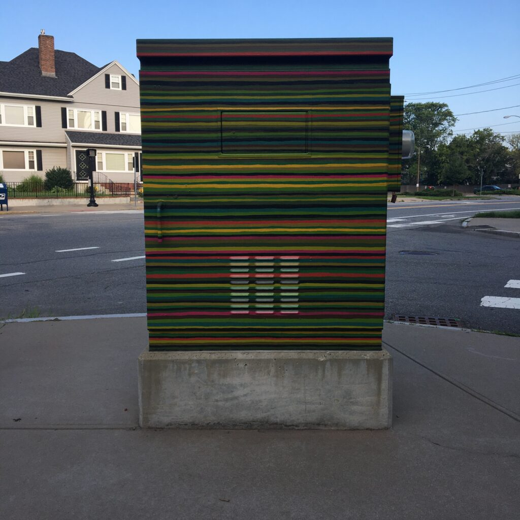 Electrical utility box on the street, painted with vibrant horizontal lines